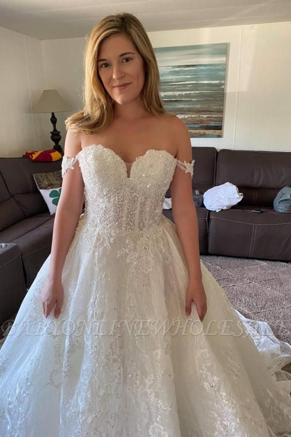 Wunderschönes schulterfreies Brautkleid mit weißen Spitzenapplikationen und Perlen